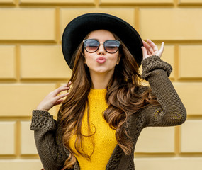 Fashion woman in a hat and sunglasses, in knit dress and jacket