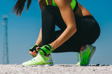 Running shoes - closeup of woman tying shoe laces. Female sport