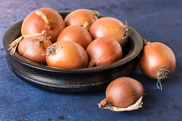 Onions.  Onions in a wooden bowl on a blue background.