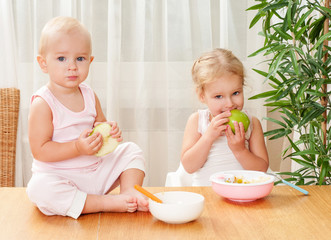 Two charming sisters babies eat a meal in the kitchen. Feeding b