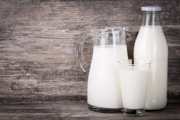 Milch in Krug, Flasche und Glas auf Holz Hintergrund.