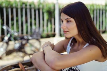 attraktive junge frau sitzt draußen auf einer bank