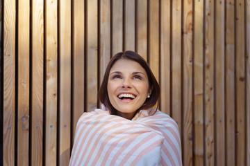 glückliche frau im spa wickelt sich in ein handtuch