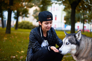 Girl feed the dog in the autumn park. Walking concept. Asian in black cap and coat. Urban style.
