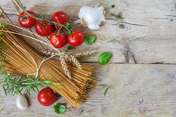 Ingredients for an Italian pasta meal with wholemeal spaghetti from above, rustic wooden background