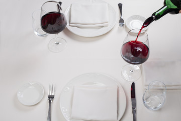 served table restaurant wine being poured into glass, white tablecloth, plates and cutlery
