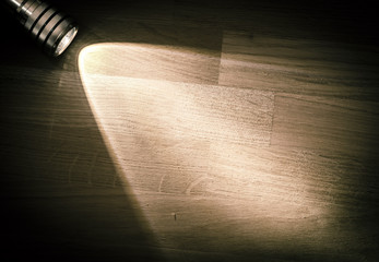 Flashlight and a beam of light in darkness. A modern led light with bright projection on dark wood table. Surface with copy space.