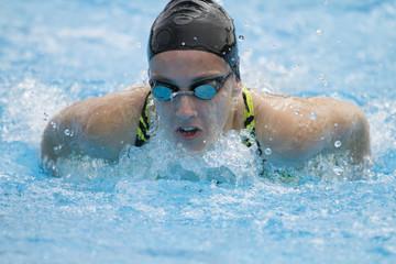 Nadadora profesional entrenando en piscina al aire libre estilo mariposa