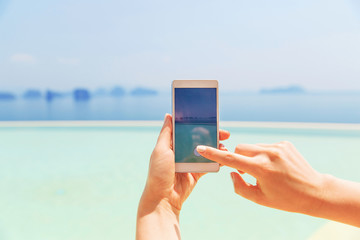close up of female hand with smartphone on beach