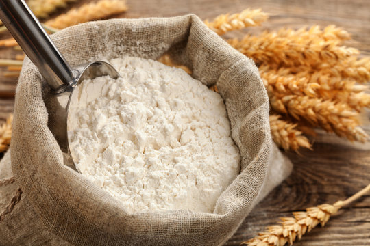 Wheat flour in a bag with wheat spikelets .