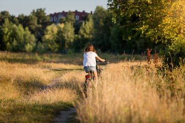 Woman riding bicycle at meadow on dirt road at sunset