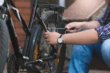 Closeup of young man repairing bicycle rear wheel