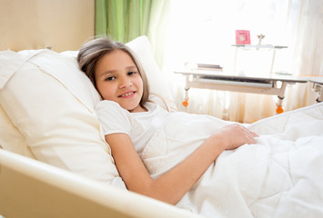 Portrait of smiling girl lying in bed at sunny morning