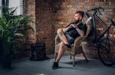 The bearded hipster male relaxing in a chair.