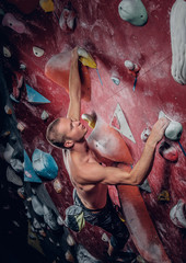 Shirtless male on a climbing wall.