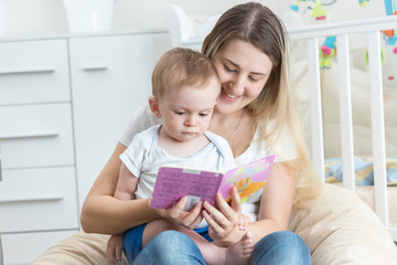 Beautiful smiling mother reading book to her 9 months old baby b
