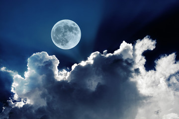 Big full moon in night sky with beautiful white clouds glowing in the moonlight
