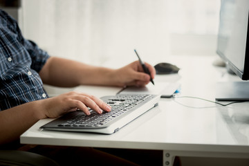 Toned photo of graphic designer using tablet and keyboard at wor
