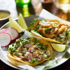 authentic mexican street tacos with chopped pork, cilantro and onion