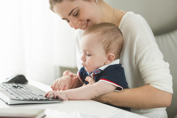 Young woman taking care of baby at office