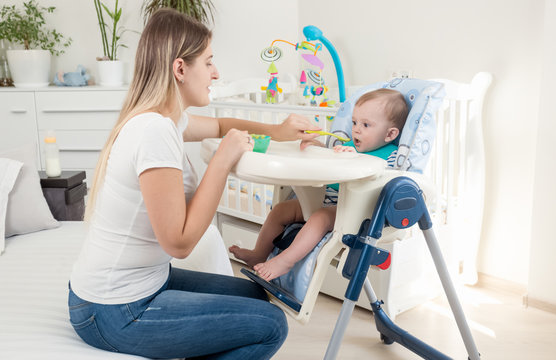 Mother feeding her baby in highchair at living room