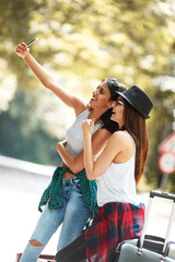 Two Young Tourist Girl Hitchhiking On The Road.Taking a selfie.