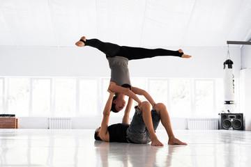 Couple practicing acro yoga in white studio. Acro yoga concept.