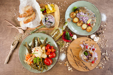 Salted fish, vegetables, bread, olive oil and other spices, condiments, meals and snacks on the wooden background