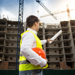 Rear view image of young engineer pointing at building with blue