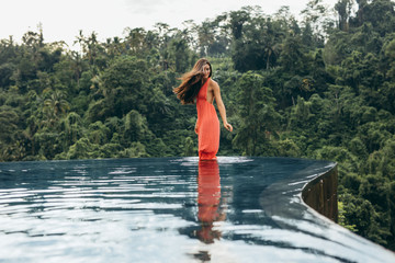 Young woman standing in infinity pool