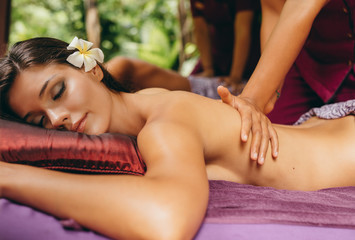 Woman having massage in tropical spa resort