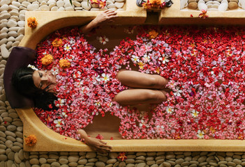 Woman having flower bath at spa