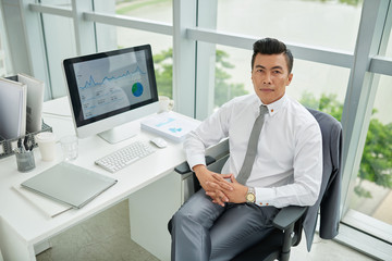 Businessman sitting at his workplace and looking at camera