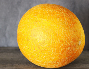 the whole yellow melon on a gray background