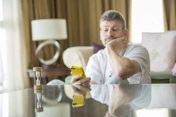 middle aged man looking at a phone, tired of waiting