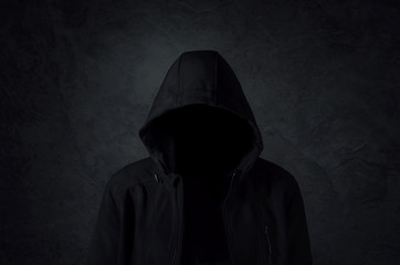Hooded man over dark concrete background