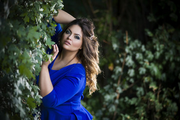 Young beautiful caucasian plus size model in blue dress outdoors, xxl woman on nature
