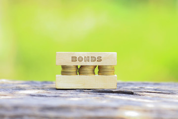 Business Concept -BONDS WORD, Golden coin stacked with wooden ba