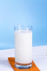 Glas Milch vor hell blau Hintergrund.