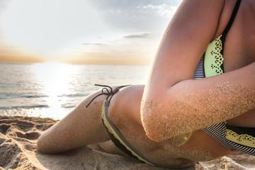 Women's sexy body on the yellow sand beach