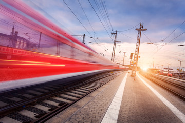 High speed red passenger train on railroad track in motion at beautiful sunset. Blurred commuter train. Railway station in the evening. Railroad travel, railway tourism. Industrial landscape. Train