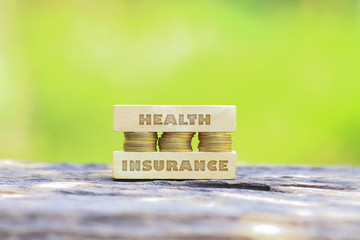 Business Concept - HEALTH INSURANCE WORD, Golden coin stacked