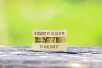 Business Concept - INSURANCE POLICY WORD, Golden coin stacked with woooden bar