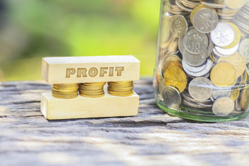 Business Concept - PROFIT WORD Golden coin stacked with wooden bar