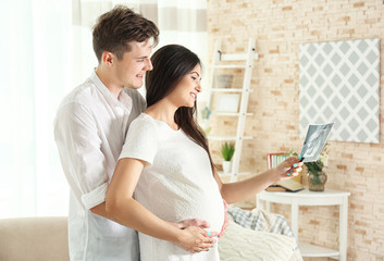 Beautiful young pregnant couple looking at ultrasound image