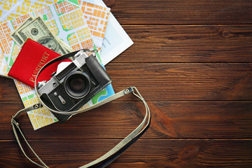 Vintage camera with map, passport and cash on wooden background