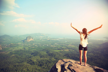 young freedom woman open arms on mountain peak Wall mural