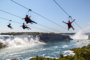 Four unrecognizable people taking zipline ride at Niagara Falls, Ontario. New zipline in Niagara Parks opened in the summer of 2016