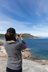 hipster woman on rock  beach taking photo with camera for  blue