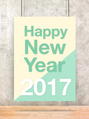 Happy new year 2017 on cream and green pastel poster hanging on